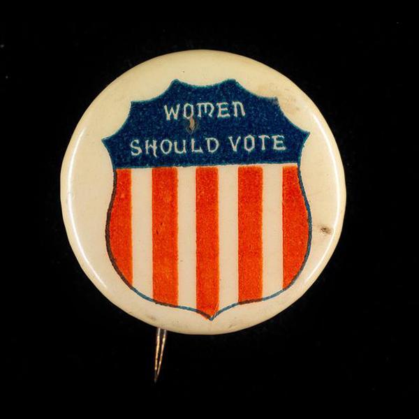 """Botão do sufrágio feminino que diz """"Mulheres devem votar"""" com uma imagem de escudo com as cores vermelha, branca e azul da bandeira americana."""