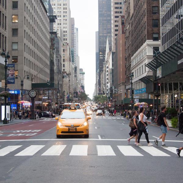 Una intersección en Nueva York con un taxi amarillo se detuvo en un semáforo y cinco peatones cruzando la calle.