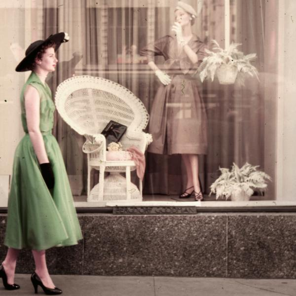 Woman walking past a department store window display.