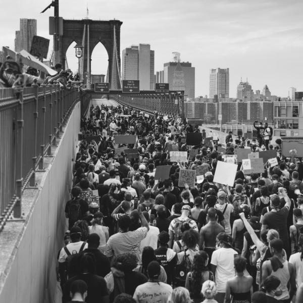 Black and white photo of protestors walking across the Brooklyn Bridge