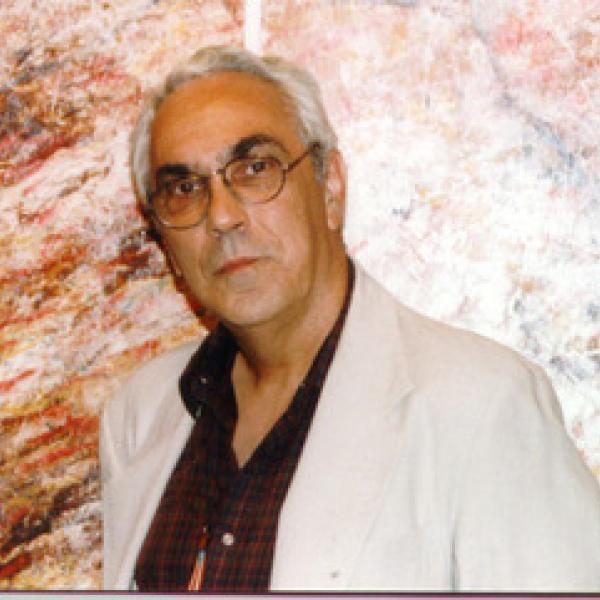 Color photograph of Mario César Romero wearing a white suit jacket and burgundy button down shirt against a brown-marbled wall