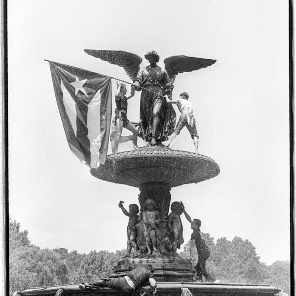 A fountain with a statue holding the Puerto Rican flag