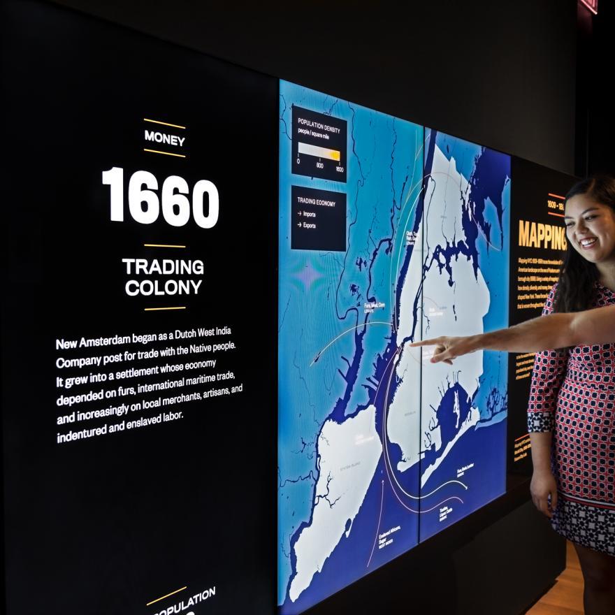 两名访客在展览空间的屏幕上指出细节