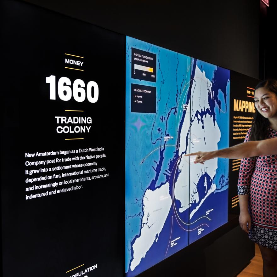 Two visitors point out details on a screen in an exhibition space