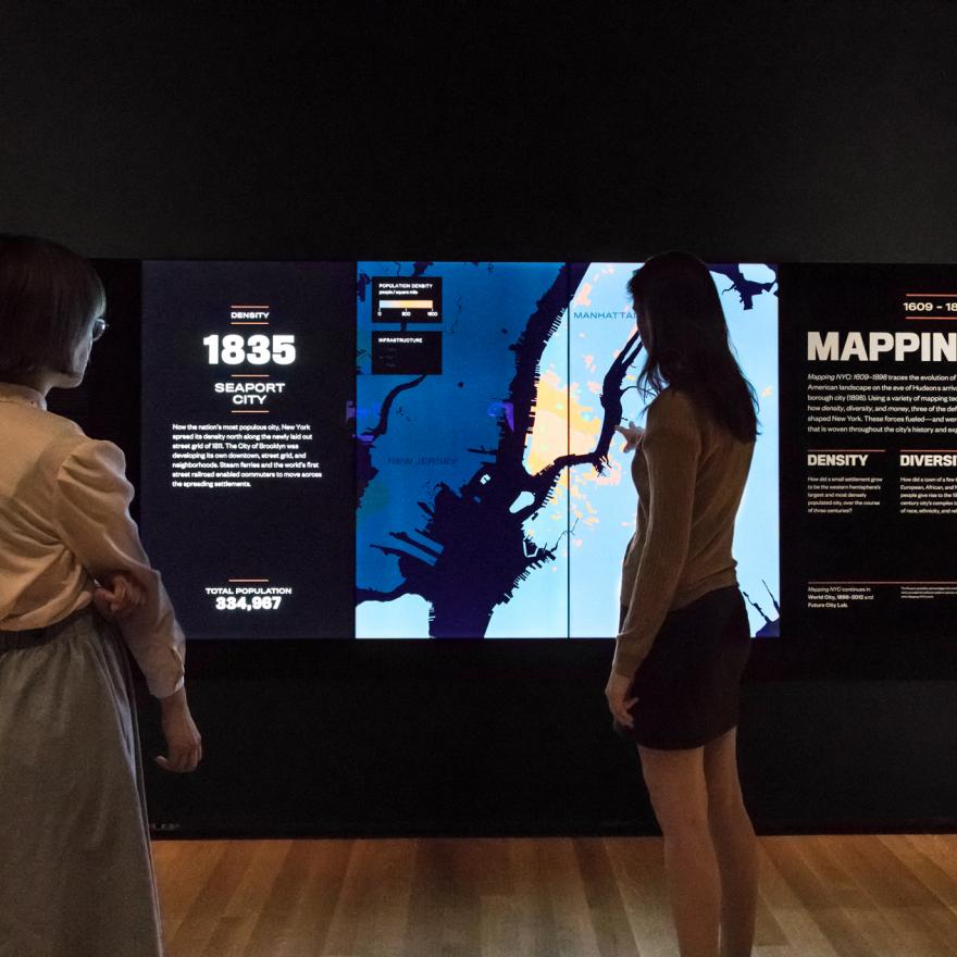 Two visitors look at a changing screen on display in a gallery