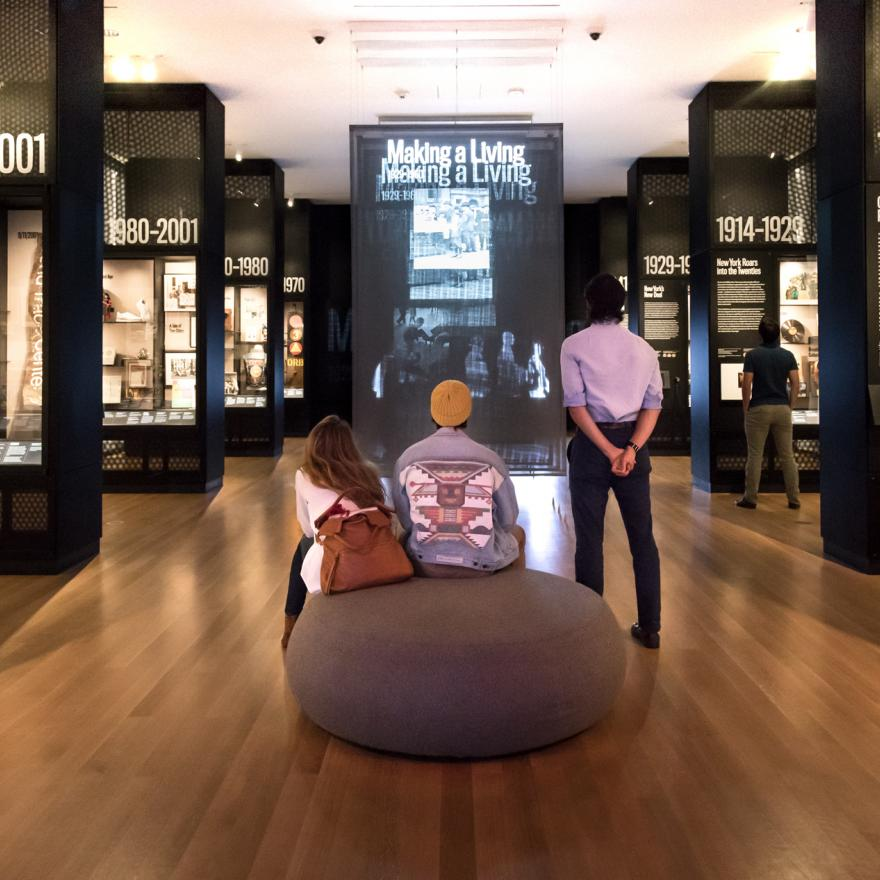 Visitors sit and stand while looking at a video display in a gallery