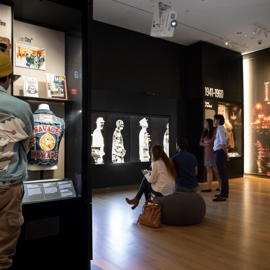Visitors look at objects on display and interactive digital components in an exhibition