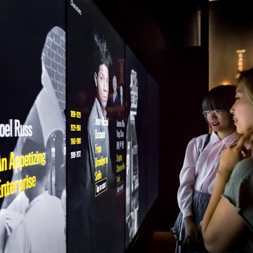 Two visitors look at interactive screens on display in a gallery