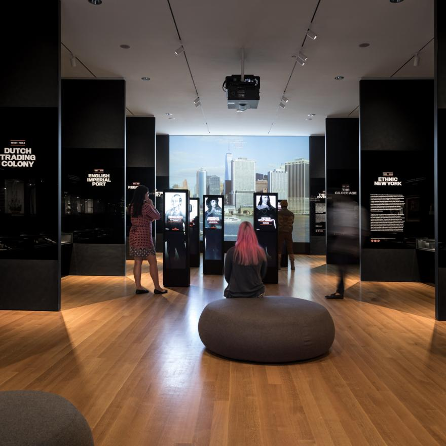 Visitors sit and stand around an exhibition at the Museum of the City of New York
