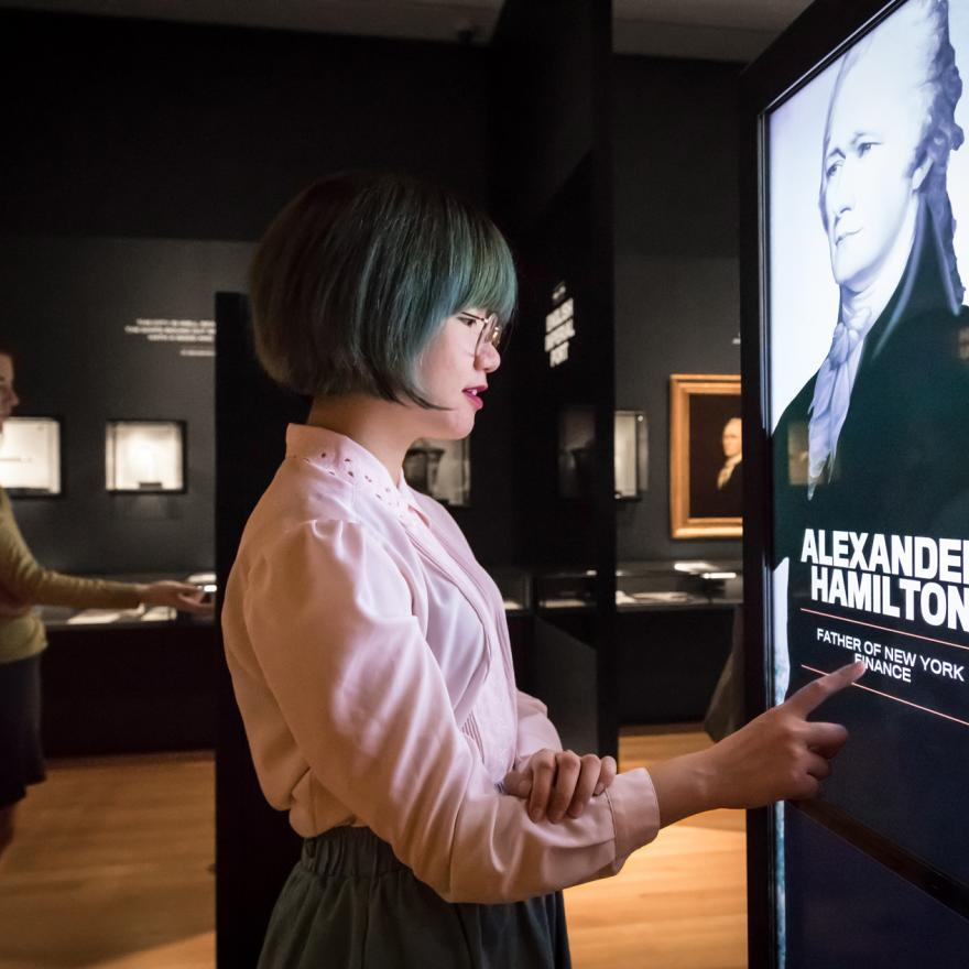Two visitors examine an interactive feature in an exhibition space