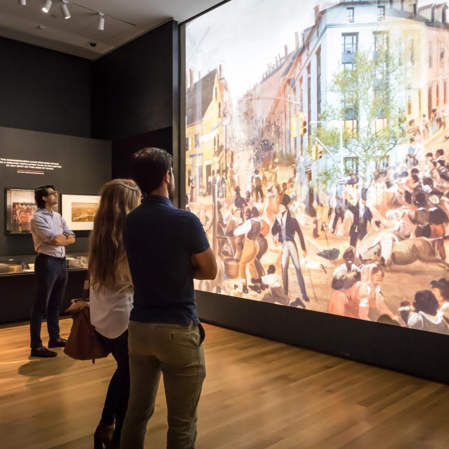 Les visiteurs regardent une grande projection dans un espace d'exposition