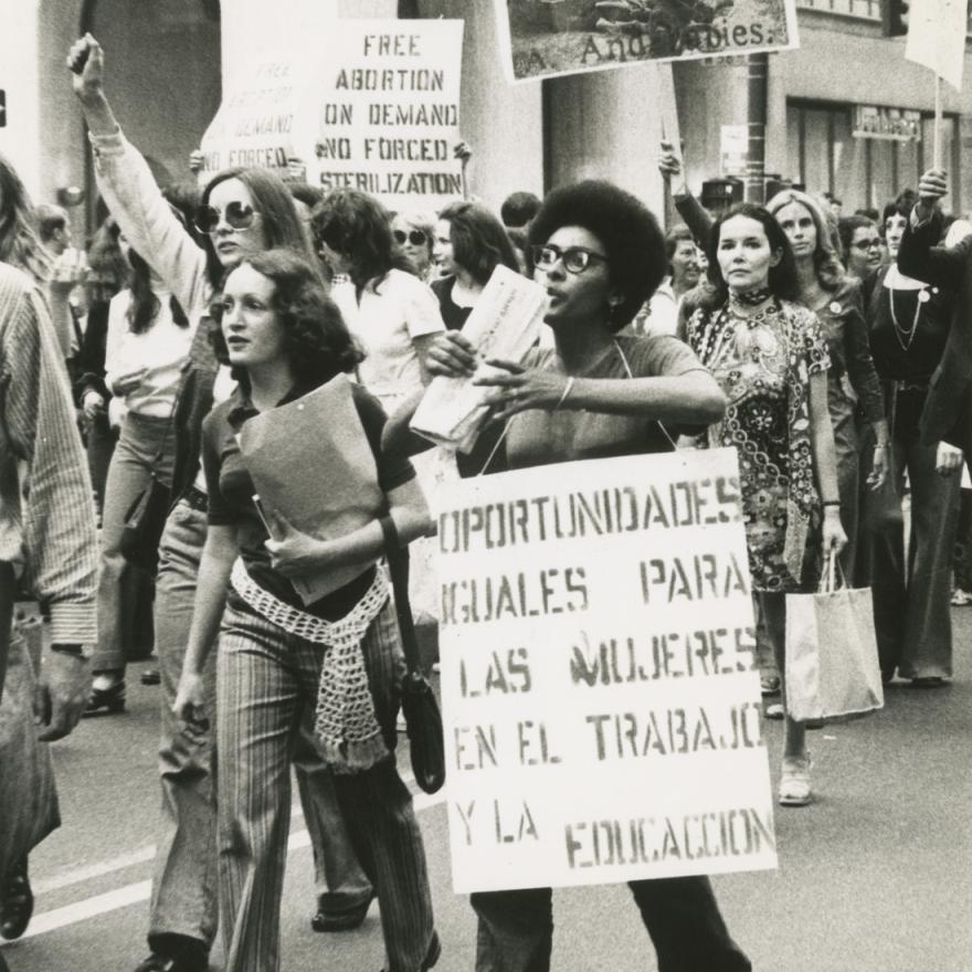 Un grupo de mujeres marcha en una manifestación, muchas tienen carteles de protesta.