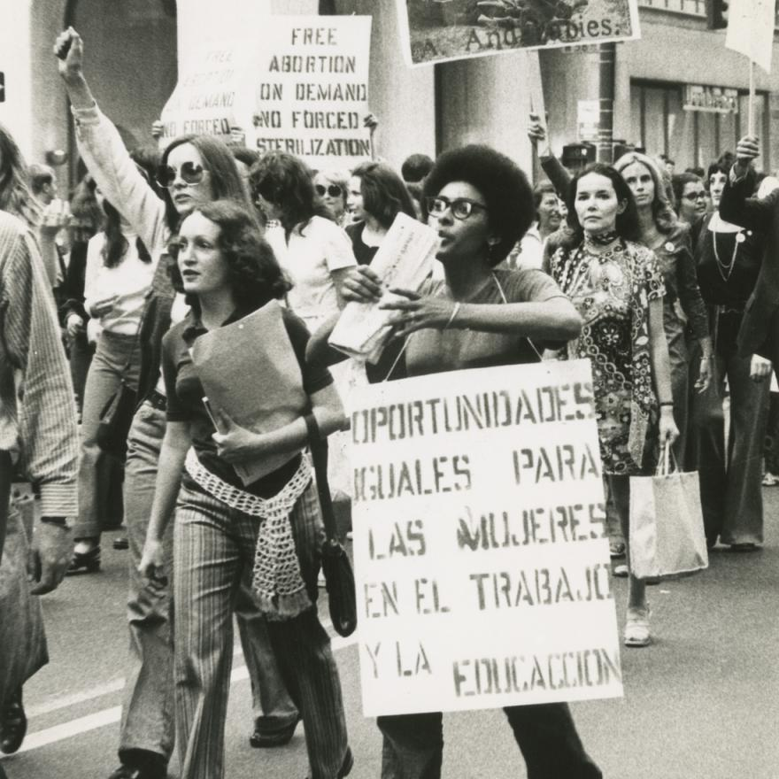 A group of women march in a rally, many are holding protest signs