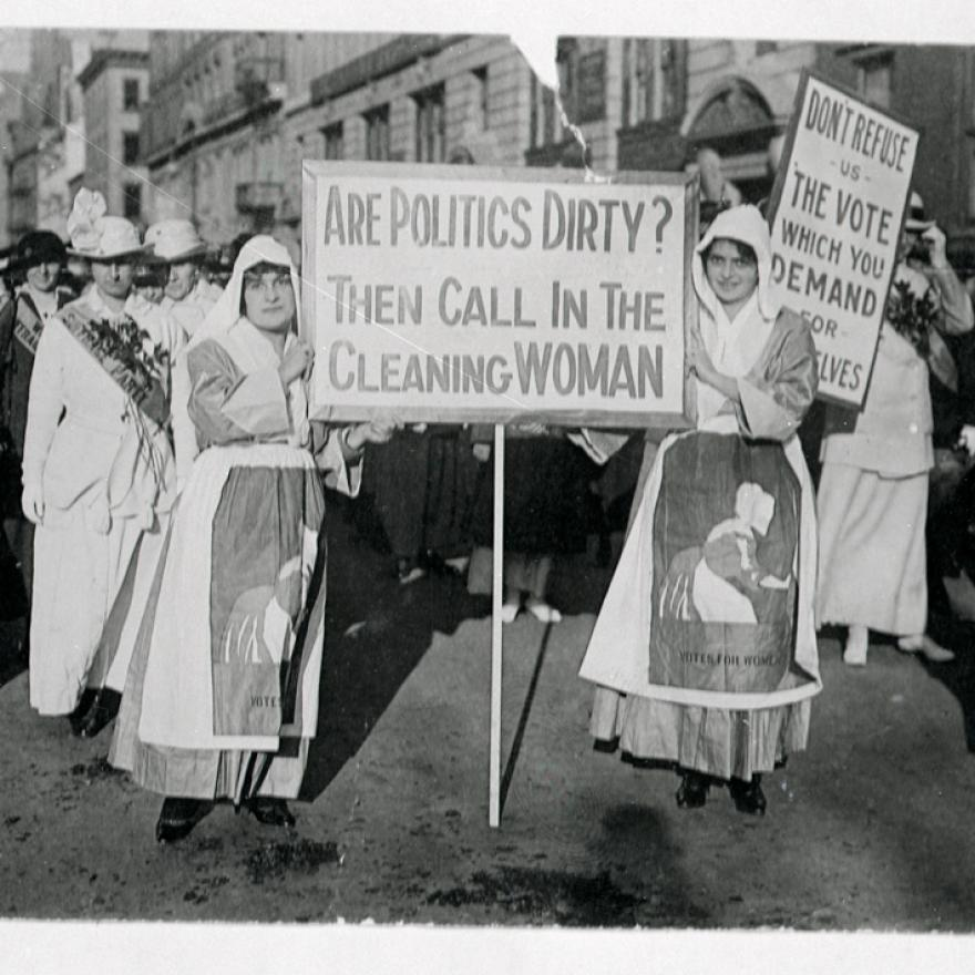 "During a suffrage rally two women face the camera with a sign that says ""Are politics dirty? Then call in the cleaning woman"""