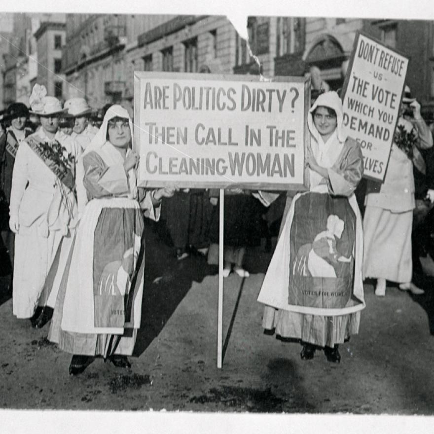 """Durante una manifestación por sufragio, dos mujeres miran a la cámara con un letrero que dice: """"¿Están sucias las políticas? Entonces llama a la mujer de la limpieza """""""