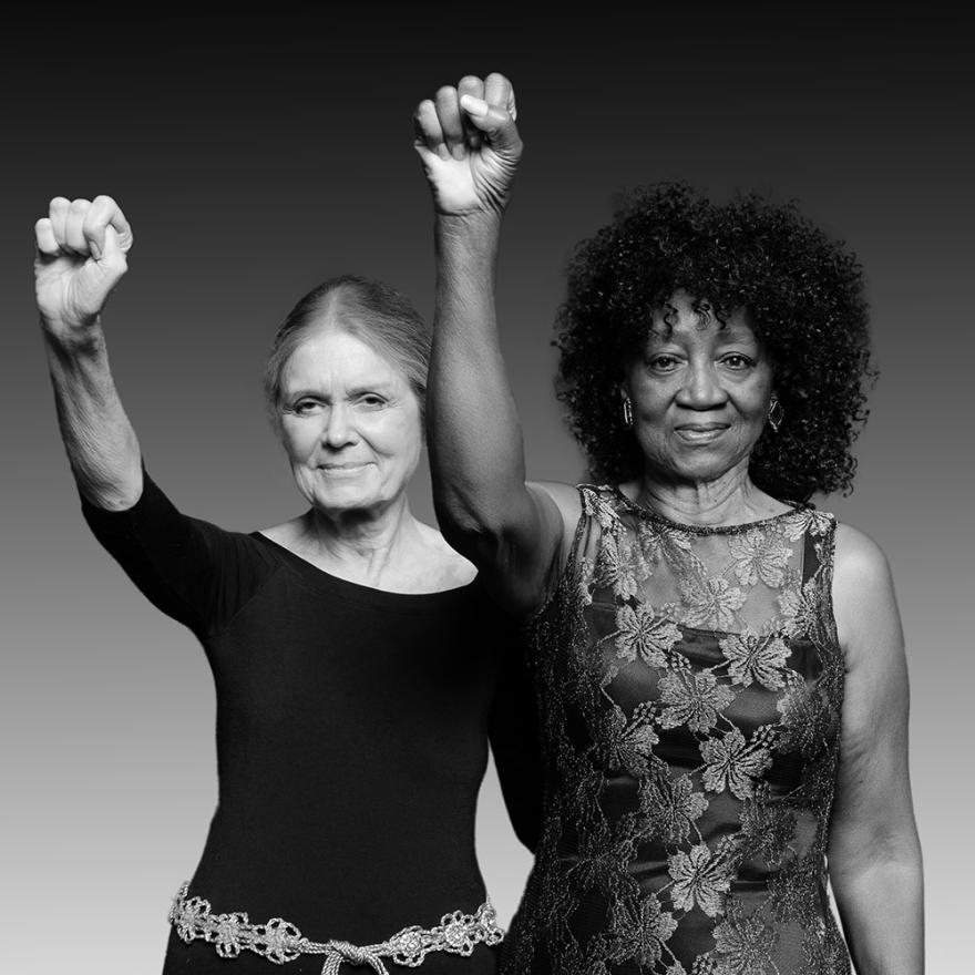 Dos mujeres mayores se enfrentan a la cámara, cada uno de sus brazos derechos se levanta en un puño
