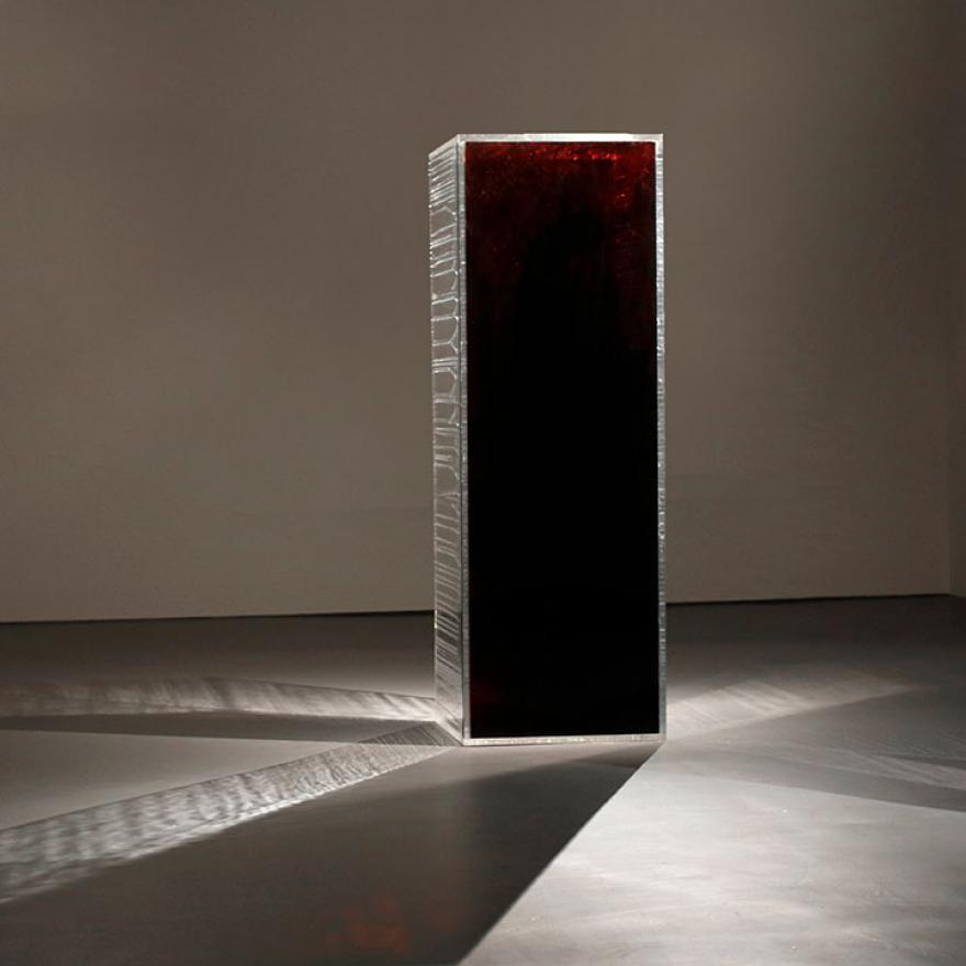 Rectangular prism that is reflective on two sides, and blood-red on the side facing the camera. Light is reflecting off it