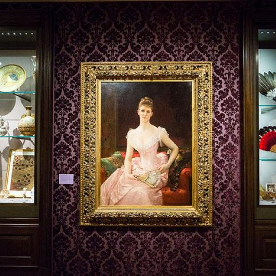 Two exhibition cases containing dishware and fans. In-between them is a painting of a seated woman in a pink dress