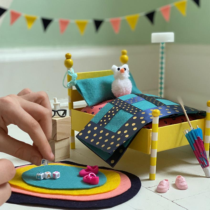 A photograph of a colorful set of miniature bedroom furniture, including a bed with stuffed animal, nightstand, rug, and decorations. An adult's hand holding a tiny block is entering the view from the left, as if about to place it on the rug.