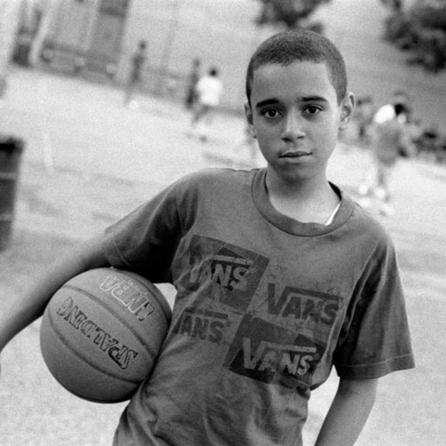 A boy stares into the camera while holding a basketball. Behind him, other children are playing basketball on a court