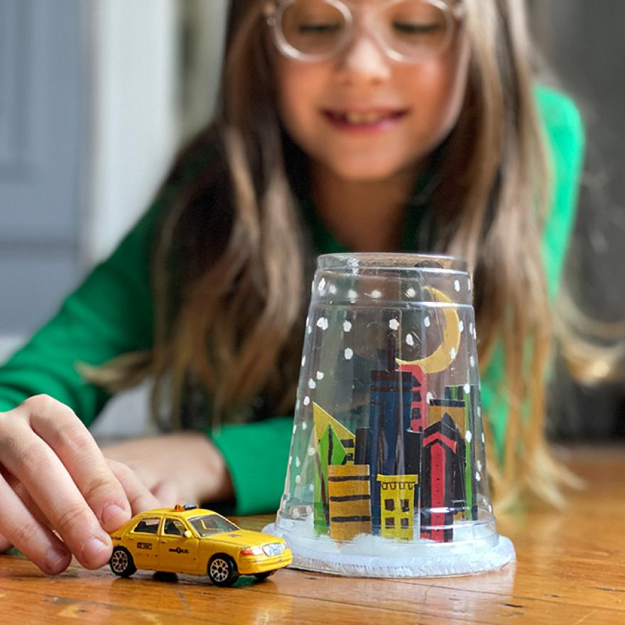 A young girl pushing a toy NYC taxi cab next to a snow globe made of a plastic cup with a hand-drawn city skyline  inside.