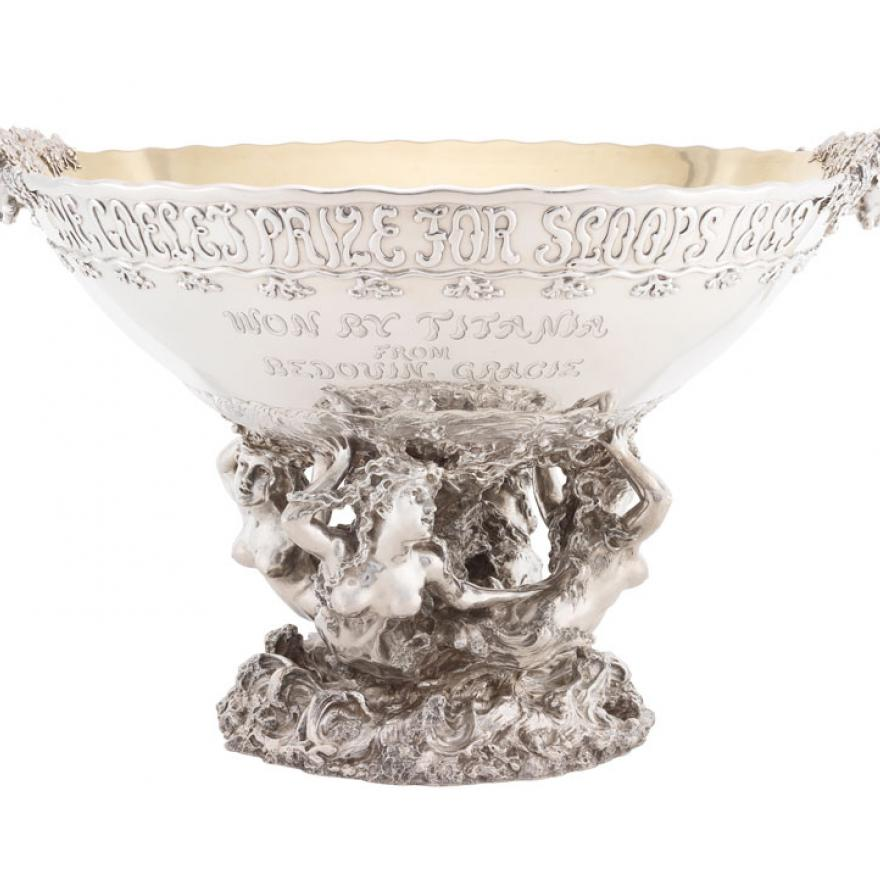 A large silver bowl held by statues of mermaids, with heads as handles and text on the bowl