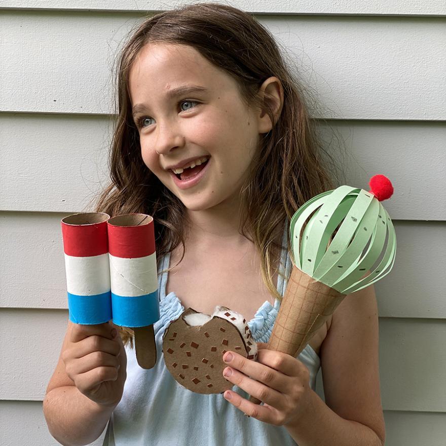 imagem de uma menina segurando sobremesas congeladas usando papel e materiais reciclados