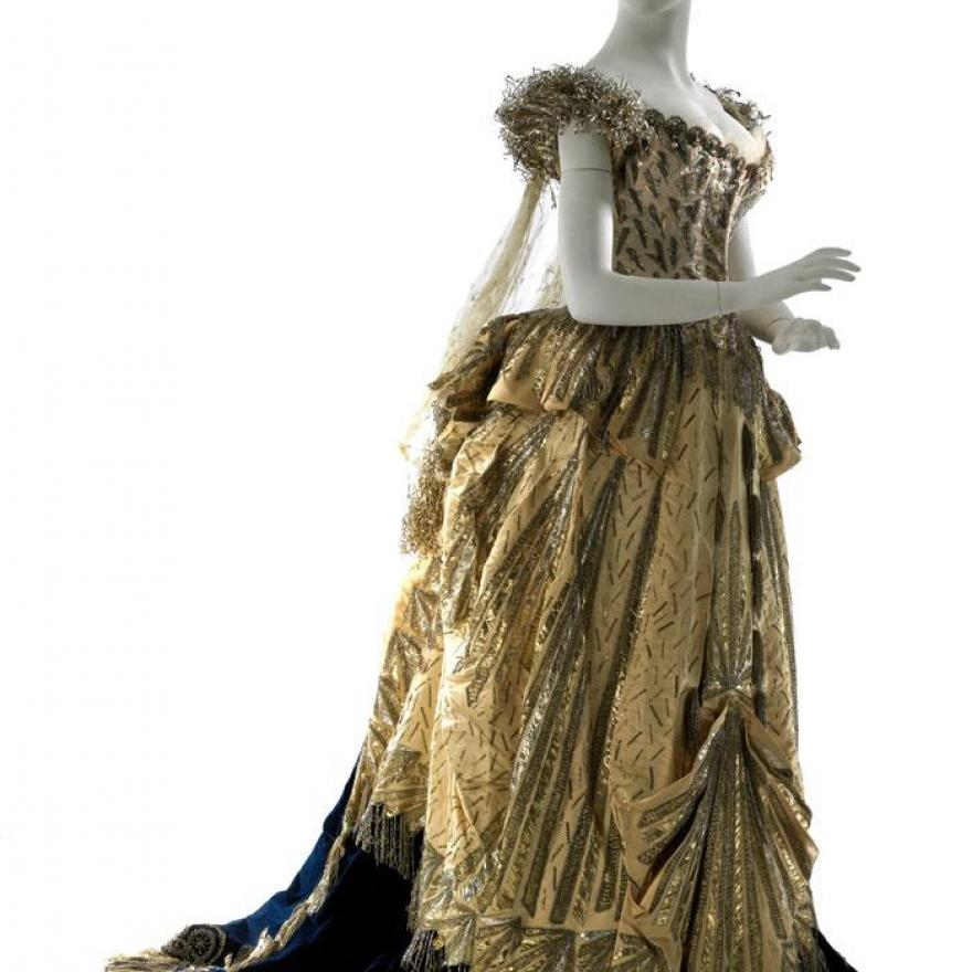 金色落地连衣裙,带有金属感细节,黑色短裙和蓝色火车