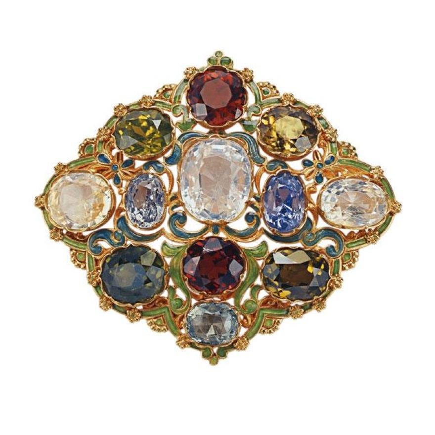 金属制成的胸针,涂成绿色和蓝绿色,带有金块和边缘。 金属中镶嵌了许多大宝石