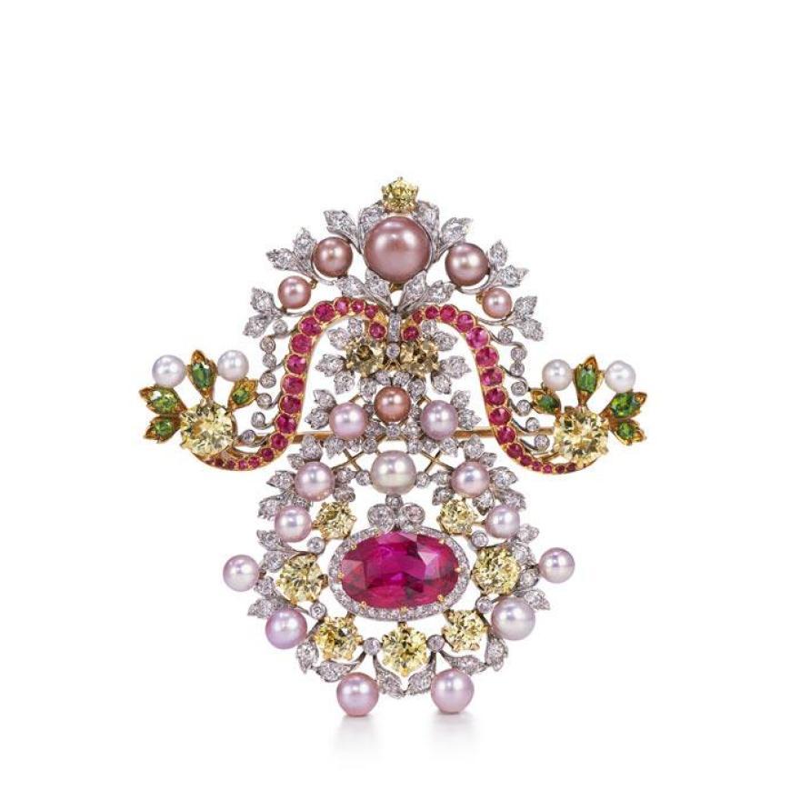 由金属制成的胸针,上面有粉红色,黄色和绿色的钻石,粉红色和白色的珍珠以及银叶