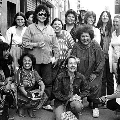 Fotografia de artistas da exposição, Women of Sweetgrass, Cedar and Sage, amigos e membros da comunidade do lado de fora da American Indian Community House Gallery tirada em 1985.