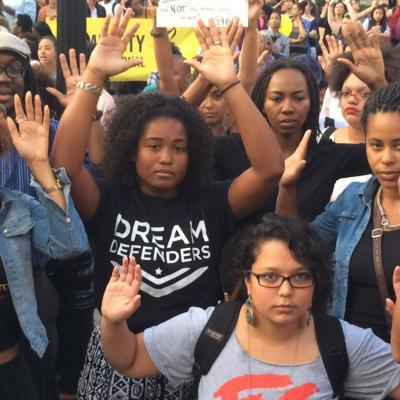 "Black Lives Matter protesters with their hands in the air in a sign of surrender and the ""hands up don't shoot"" slogan"