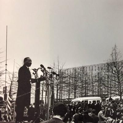 De uma plataforma elevada, o Rev. Martin Luther King Jr. se dirige a uma multidão reunida de jornalistas na cidade de Nova York