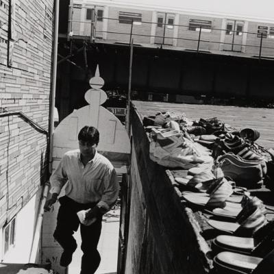 Um homem subindo escadas, pares de sapatos estão próximos, sugerindo que ele está indo a uma mesquita para rezar