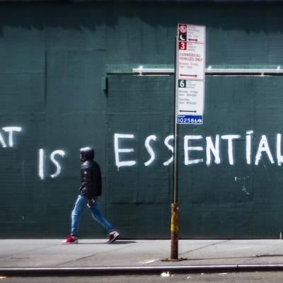 "A man walks by a boarded up wall with the words ""What is essential"" spray painted across it."
