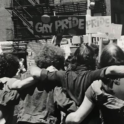 Fotografia de Fred W. McDarrah de um grupo de pessoas abraçadas e segurando cartazes relacionados ao Orgulho