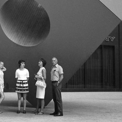 Cuatro personas se paran en la acera frente a una gran estatua de un cubo con un agujero que atraviesa el centro.