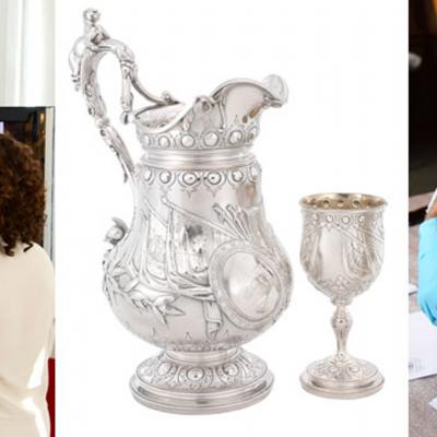 A man points out details on a silver vase; an elaborate silver pitcher and goblet; two people examine a silver object