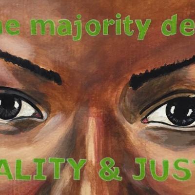 """Pintura dos olhos de uma mulher. Pintadas na testa e nas bochechas estão as palavras """"nós, a maioria, exigimos / IGUALDADE E JUSTIÇA"""""""