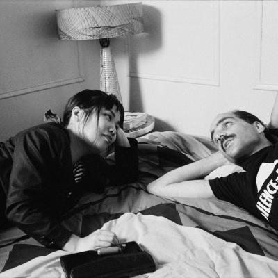 A female caregiver and male AIDS patient wearing an ACT UP t-shirt lie on a bed together looking into each other's eyes