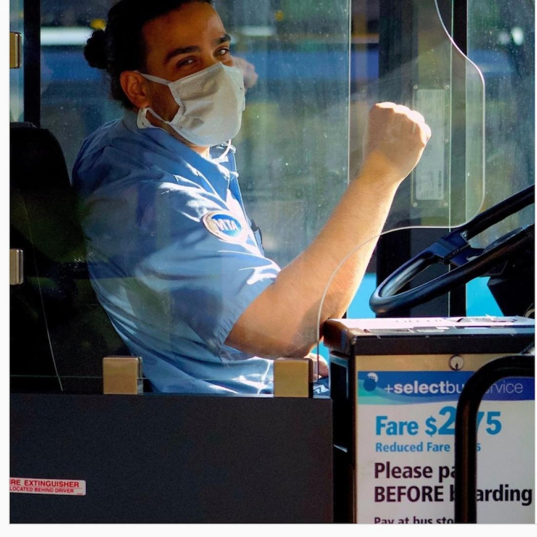 A bus driver wearing a mask sits at the wheel of a bus with his fist slightly raised.