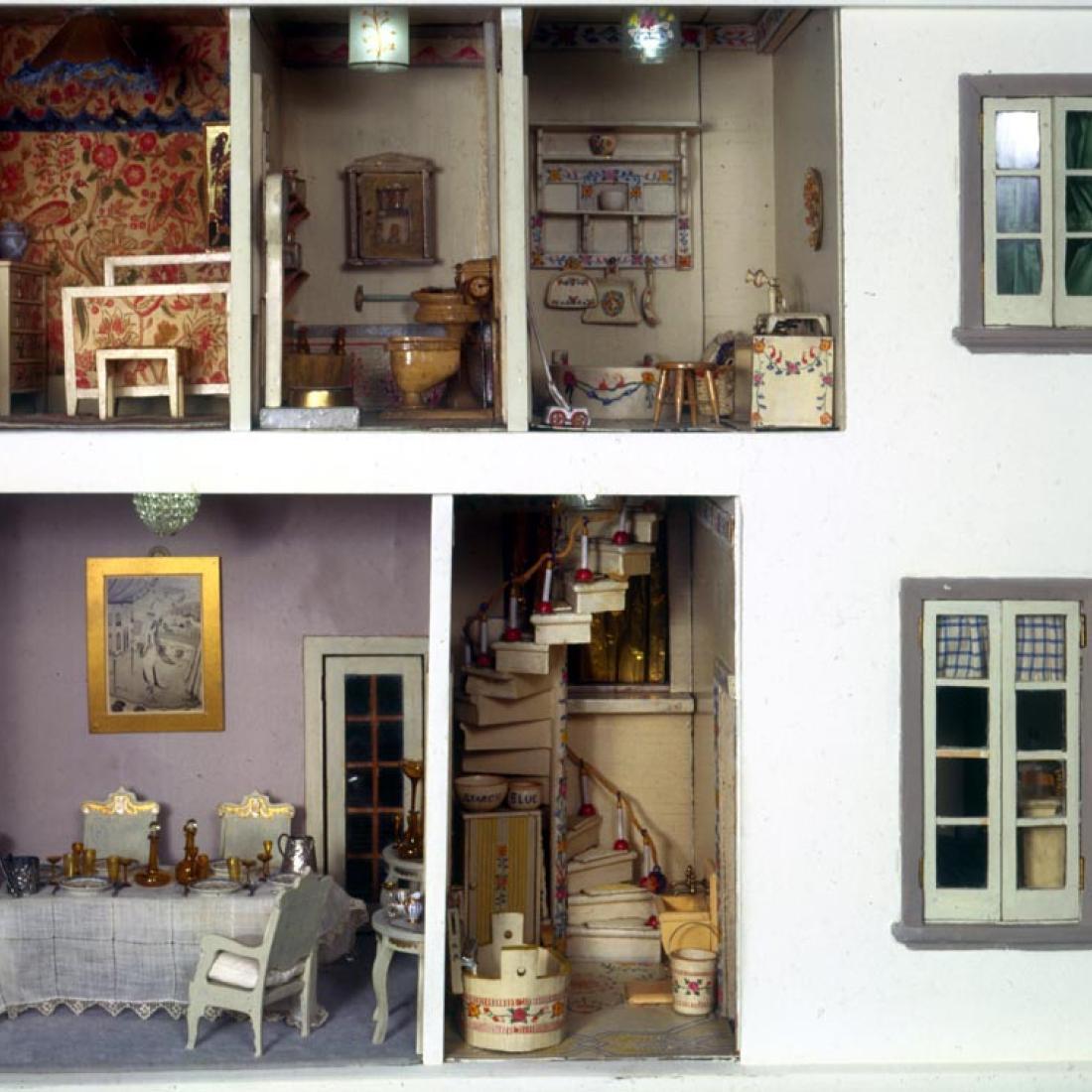 Vue de deux fenêtres, d'un escalier et d'une salle à manger, d'une salle de bains et d'une chambre meublées dans la maison de poupée Stettheimer