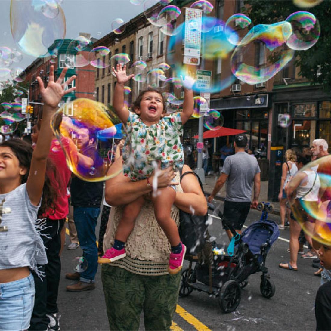 Miembros de la comunidad Park Slope en la calle jugando con burbujas.