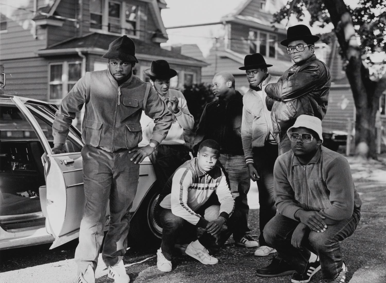 RUN DMC com um grupo de homens posando ao lado de um carro em Hollis, Queens.