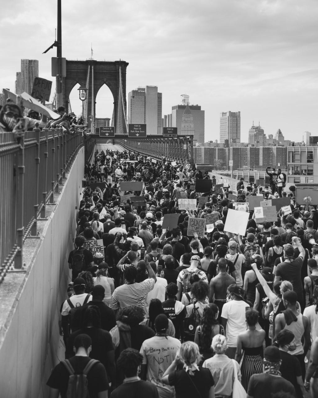 Black and white photo of protestors walking across the Brooklyn Bridge