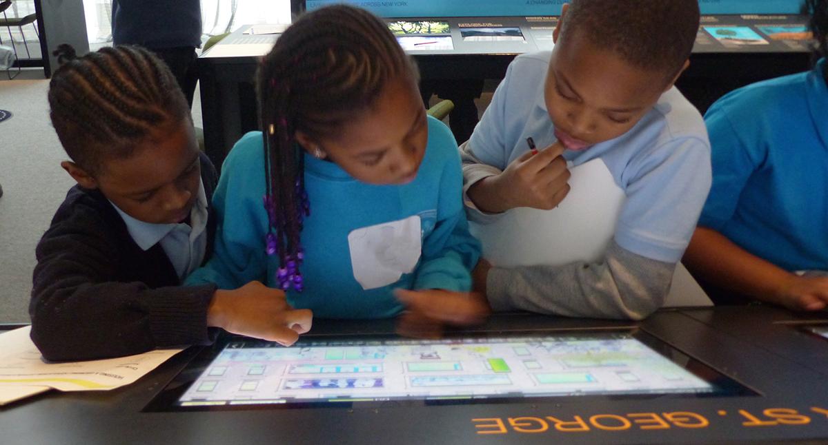 Tres estudiantes de primaria se reunieron alrededor de una pantalla de tableta en el museo, aprendiendo digitalmente