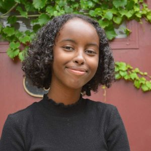 Isra Hirsi is in front of a burgundy door covered in ivy. She wears a black mock turtle neck and smiles directly at the camera.